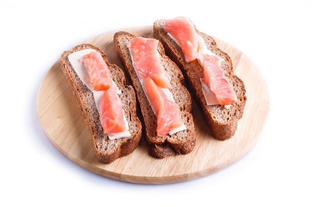 Sanduíches salmon fumados com manteiga na placa de madeira, isolada no branco.