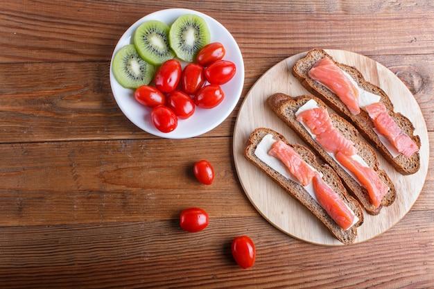 Sanduíches salmon fumados com manteiga no fundo de madeira.