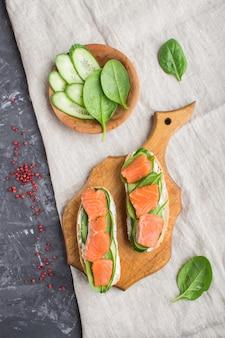 Sanduíches salmon fumados com pepino e espinafre na placa de madeira em um concreto preto.