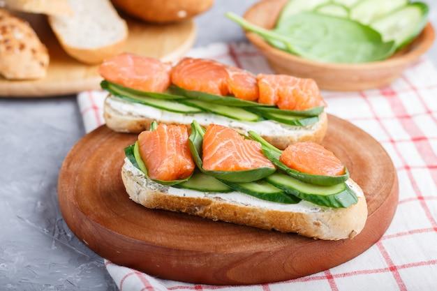 Sanduíches salmon fumados com pepino e espinafre na placa de madeira em um linho.