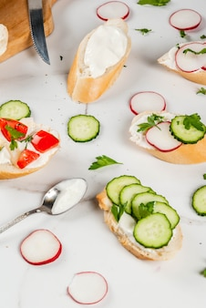 Sanduíches torradas com creme de queijo caseiro e legumes frescos