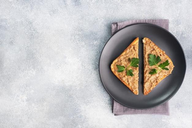 Sanduíches torradas crocantes e patê de fígado de frango com folhas de salsa em um prato preto