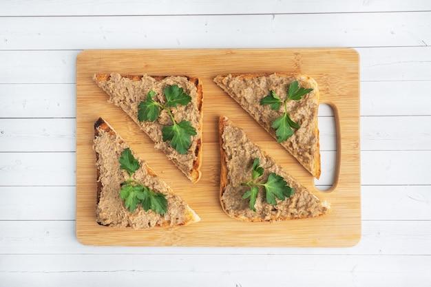 Sanduíches torradas crocantes e patê de fígado de frango com folhas de salsa em uma tábua de madeira