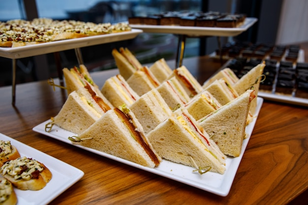 Sanduíches triangulares confortáveis na mesa de banquete.
