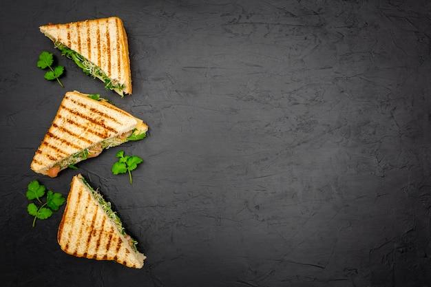 Sanduíches triangulares na ardósia com espaço de cópia
