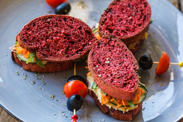 Sanduíches vegan no café da manhã com pão de beterraba, homus e legumes