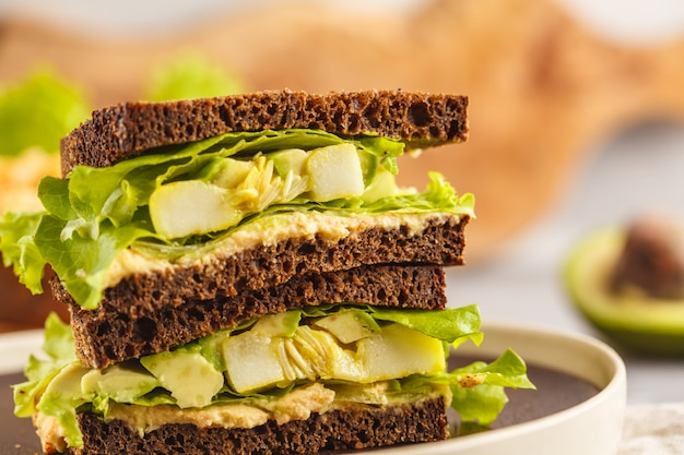 Sanduíches vegan verde com hummus, legumes assados e abacate.