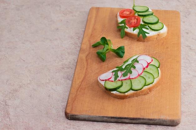 Sanduíches veganos com creme caseiro de requeijão com ervas, rabanetes, pepinos e tomates. na tábua de madeira.