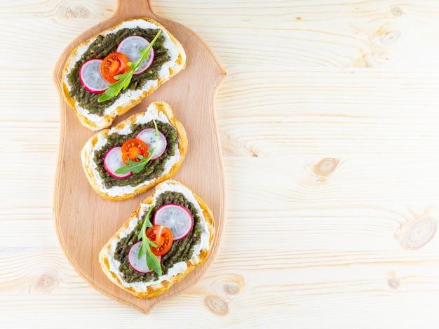 Sanduíches veganos com creme de abacate em uma tábua de cortar.