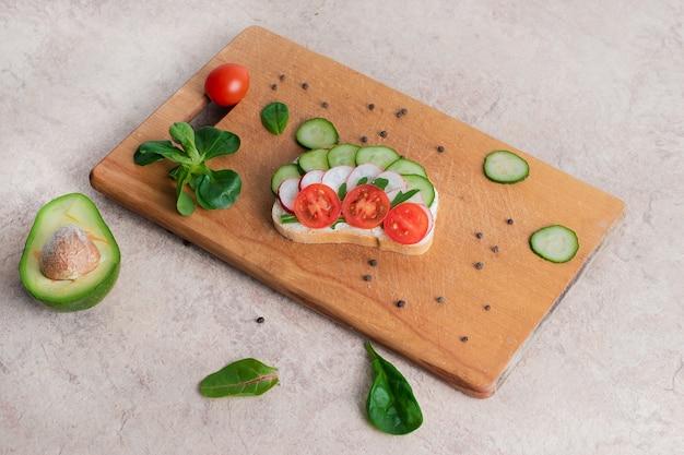 Sanduíches veganos com creme de requeijão caseiro com ervas, com rabanete, pepino, abacate e tomate. na tábua de madeira.