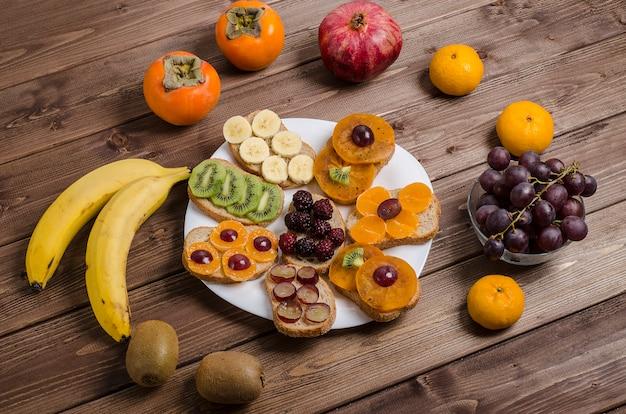 Sanduíches veganos de frutas com banana, caqui, uva, kiwi, tangerina em um fundo escuro de madeira
