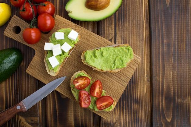 Sanduíches vegetarianos com abacate, cereja e queijo macio no fundo de madeira marrom. vista superior. copie o espaço.