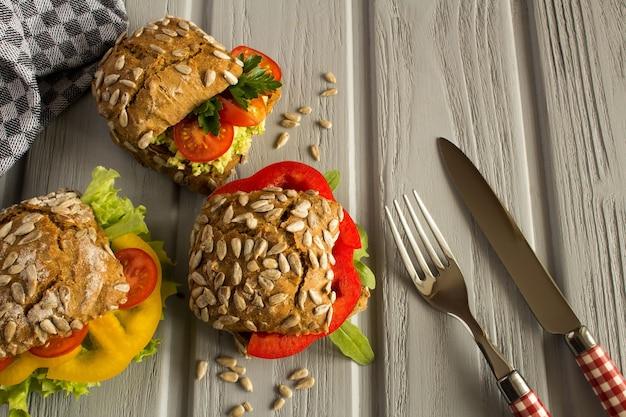 Sanduíches vegetarianos com legumes na superfície de madeira cinza. vista superior.