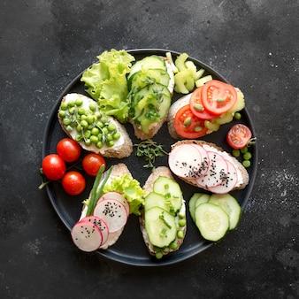 Sanduíches vegetarianos diferentes com legumes, rabanete, tomate, pão de centeio no preto. aperitivo para festa.