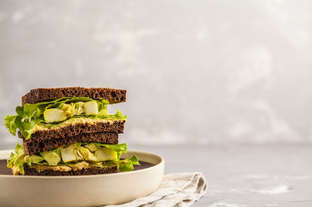Sanduíches verdes do vegetariano com hummus, vegetais cozidos e abacate, espaço da cópia.