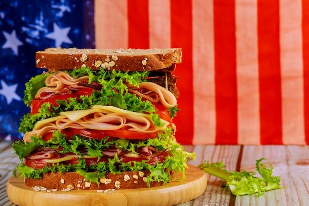 Sandwiche grande com presunto, queijo e tomate para a mesa de férias americanas