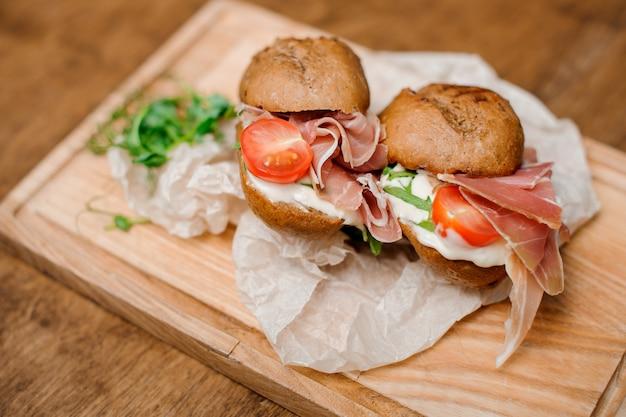 Sandwithes deliciosos com tomate vermelho e presunto saboroso