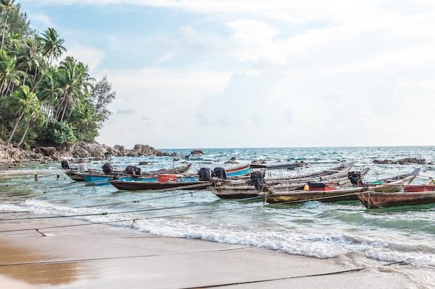 Sandy beach com os barcos de pesca coloridos no por do sol.
