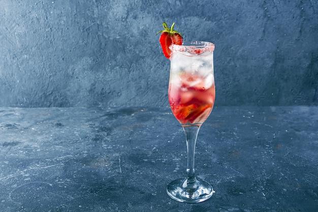 Sangria de morango com vinho, morango e cubos de gelo em taça de champanhe
