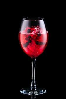 Sangria fria com bagas forrest em um copo de vinho isolado no fundo preto