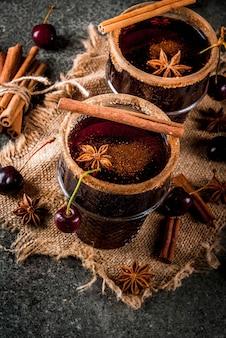 Sangria quente de cereja com canela, anis, vinho e especiarias sobre um fundo escuro e de madeira de pedra