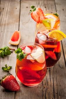 Sangria tradicional da bebida do verão - vermelho, rosa e branco. com champanhe, vinho tinto e rosa e frutas