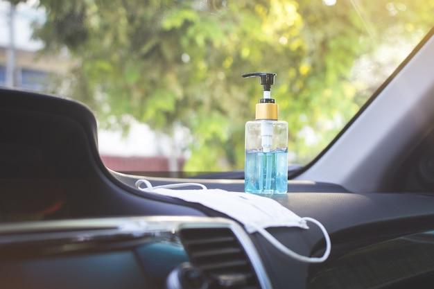 Sanitizante em gel han e máscara cirúrgica colocados na concha do carro