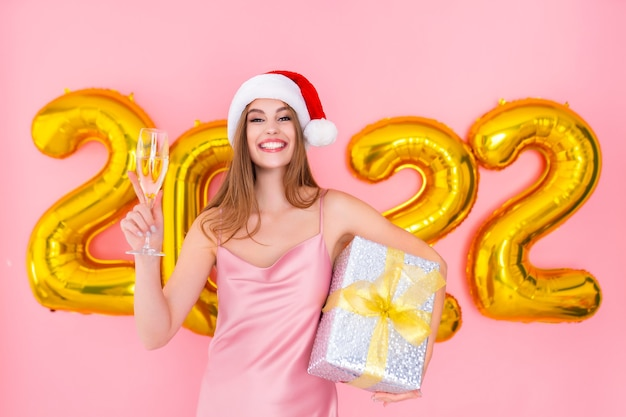 Santa animada levanta uma taça de champanhe enquanto segura uma caixa de presente com balões de ar de ano novo