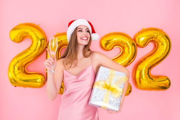 Santa animada segurando uma taça de champanhe e um presente nas mãos em balões de ar no ano novo