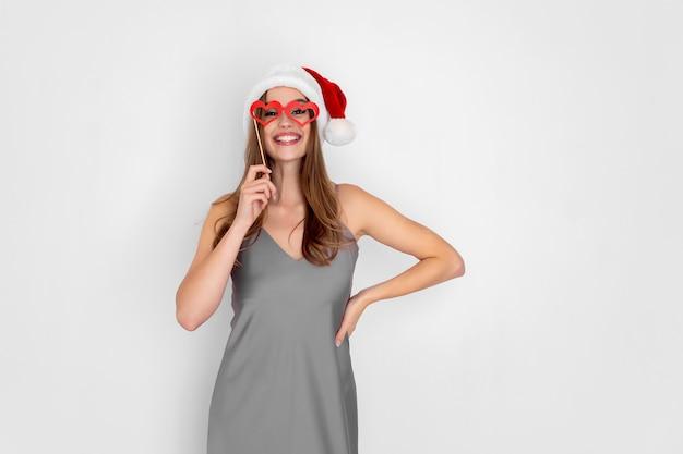Santa sorridente e engraçada usa óculos de coração de mentira, isolados no fundo branco, festa de ano novo