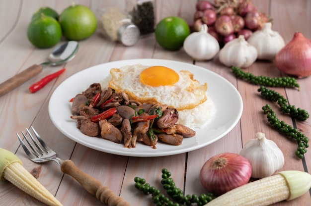 Santo manjericão arroz frito com coração de frango e ovo frito sobre um piso de madeira branco.