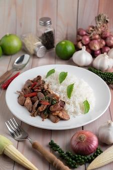 Santo manjericão arroz frito com coração de frango em um piso de madeira branco.