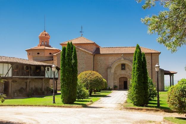 Santuário antigo com ciprestes e casa velha.