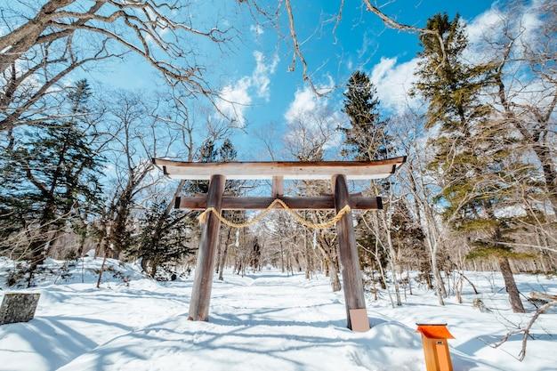 Santuário da entrada da porta de japão torii na cena da neve, japão