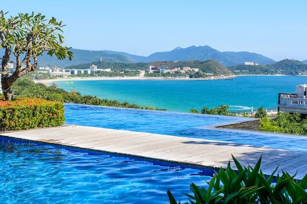 Sanya, hainan, china - 20 de fevereiro de 2020: vista do hotel para o mar azul-turquesa, montanhas, praia, jet skis, barcos a motor e paraquedas na costa da baía de dadonghai no mar da china meridional. dia de sol