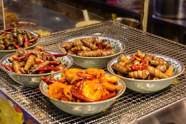 Sanya, hainan / china - 7 de janeiro de 2020: comida de rua chinesa. comércio de rua. tipos chineses de frutos do mar frescos em um mercado asiático de frutos do mar em sanya, província de hainan, china. inscrição: nomeie comida.