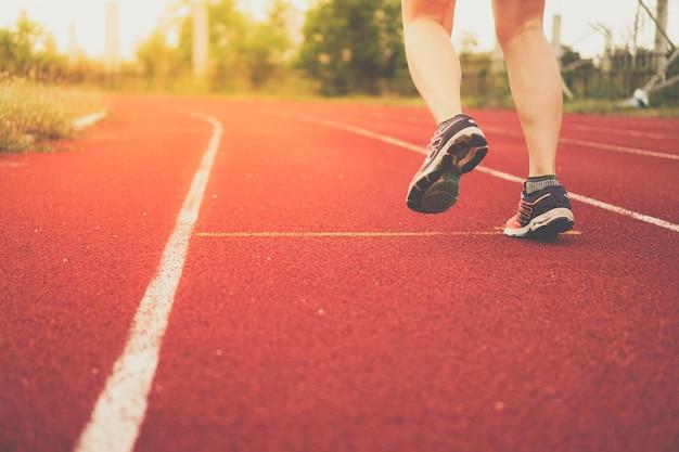 Sapata do esporte do desgaste de mulher sobre para correr no fundo running da corte.
