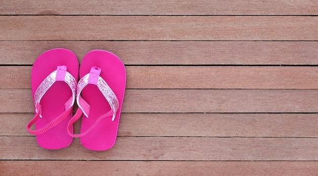 Sapatas da sandália do bebê do close-up na prancha de madeira, vista superior.