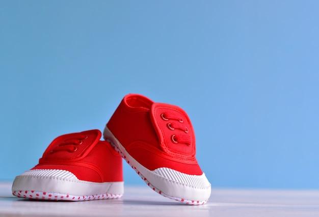 Sapatas de bebê menino vermelho no chão de madeira branco e fundo azul