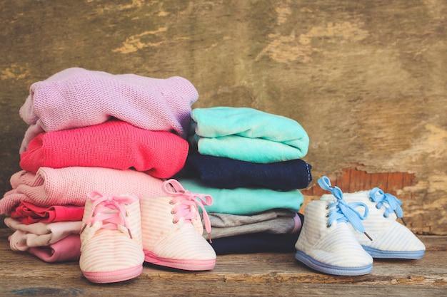 Sapatas de bebê, roupa e chupetas rosa e azul no fundo de madeira velho. imagem enfraquecida.