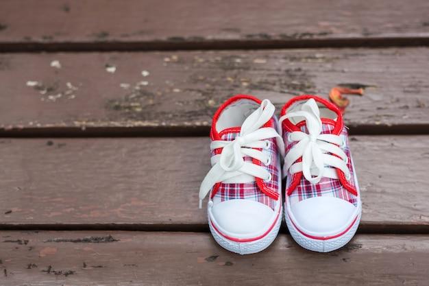 Sapatas de bebê vermelho e branco na cadeira de madeira