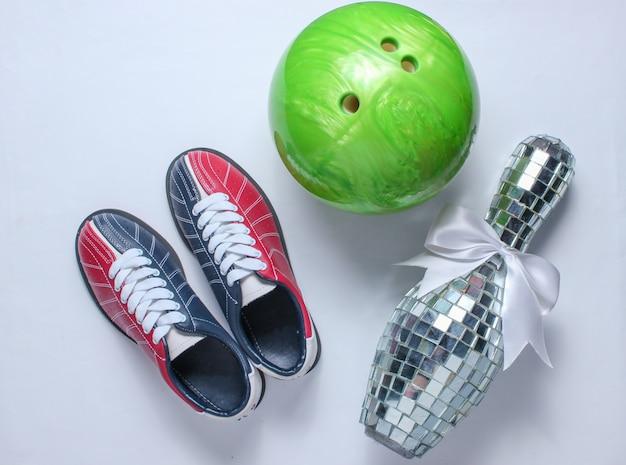 Sapatas de boliches, skittle do espelho do disco e bola de boliches no branco.
