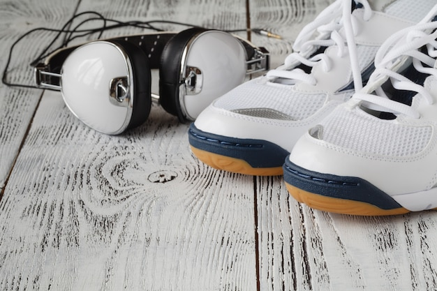 Sapatas do esporte com fones de ouvido na parede de madeira
