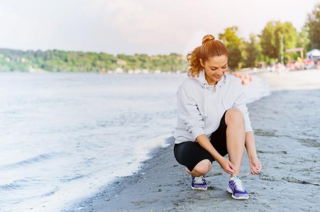 Sapatas do esporte de laço de mulher e se preparando para correr e exercitar-se na praia no verão