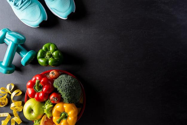 Sapatas do esporte e comida saudável na parede preta.