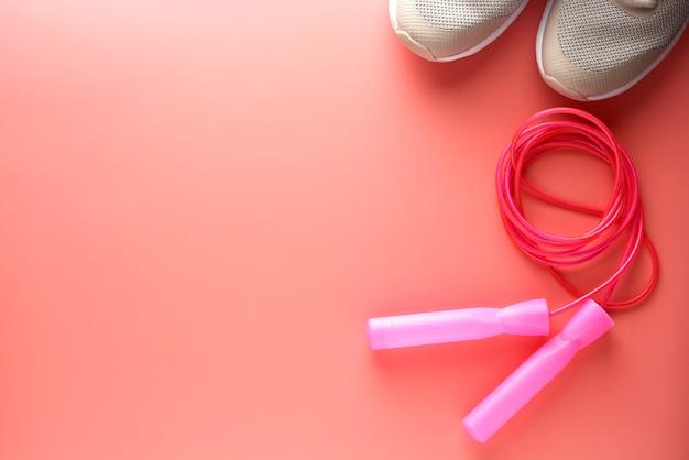 Sapatas do esporte e pular corda sobre fundo rosa