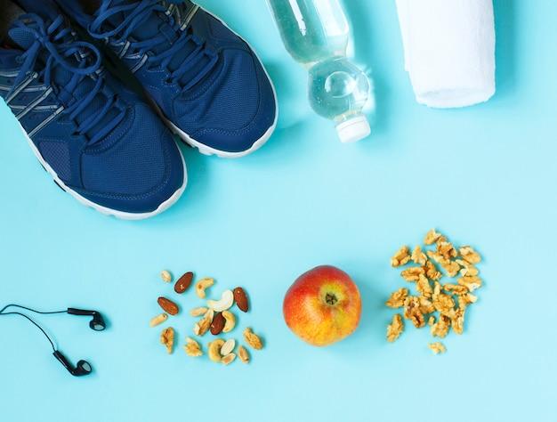 Sapatas do esporte, pular corda, nozes, fones de ouvido, maçã e garrafa de água