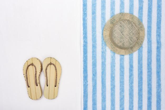 Sapatas do verão, chapéu, toalha de terry no fundo branco. fundo de verão. estilo minimalista.