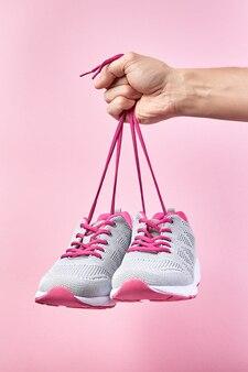 Sapatas dos esportes em fundo rosa