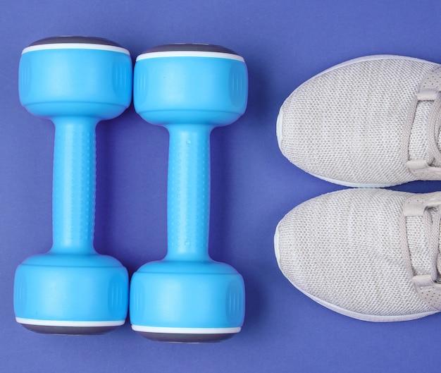 Sapatas esportivas com halteres em fundo azul, vista superior, postura plana